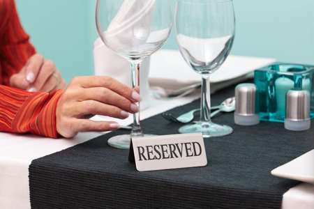 Photo of a womans hand holding a glass at a reserved table in a restaurant photo