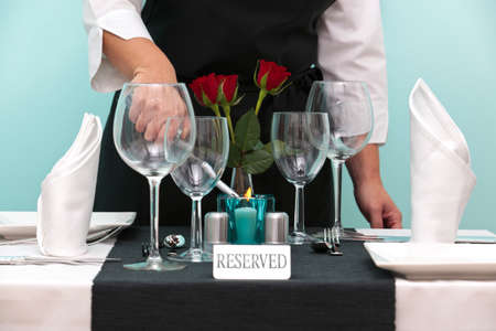 reserved: Photo of a waitress lighting a candle on a reserved table in a restaurant.
