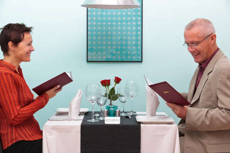 Photo of a mature couple sitting in a restaurant reading the menu Stock Photo - 12194670
