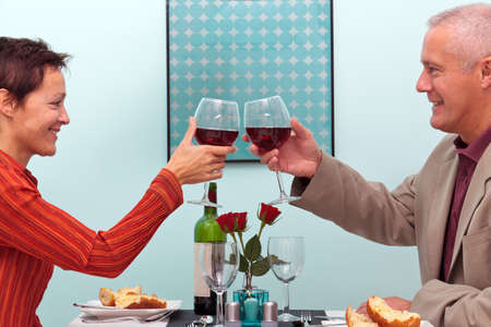 Foto van een volwassen paar het roosteren hun glazen rode wijn terwijl je in een restaurant