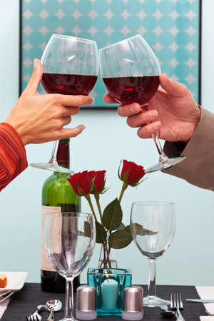 candlelit: Photo of a couples hands toasting their glasses of red wine over the table in a restaurant