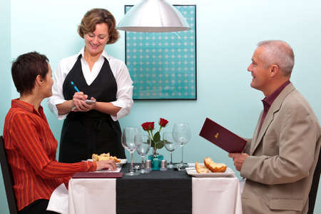 Photo of a waitress in a restaurant taking a food order from a mature couple who are sat at a table. photo