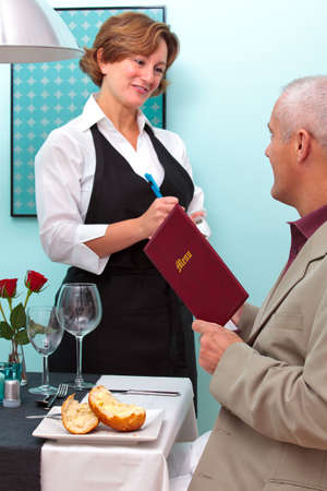 Photo of a waitress in a restaurant taking a food order from a mature male who is sat at a table holding a menu. Stock Photo - 12194687