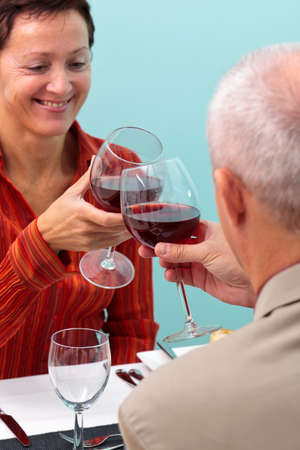 chink: Photo of a mature couple in a restaurant toasting their glasses of red wine,
