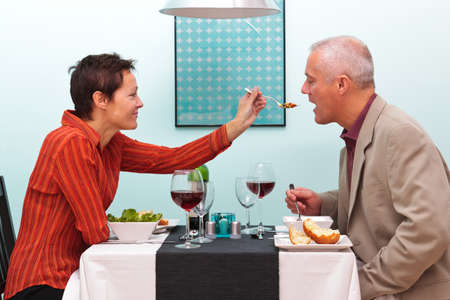 candlelit: Photo of a wife letting her husband try her food in a restaurant. Stock Photo