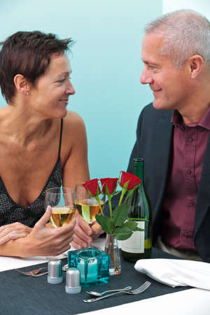 Photo of a mature married couple looking into each others eyes whilst sat at a table in a restaurant Stock Photo - 12194695