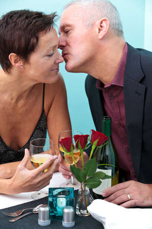Photo of a mature married couple in a restaurant, he is giving her a kiss on the cheek. photo