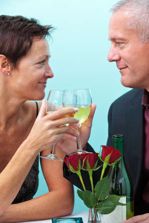 Photo of a mature married couple holding glasses of wine and looking at each other whilst sat in a restaurant. photo