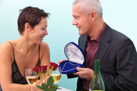 Photo of a mature man giving his wife a diamond necklace whilst sat at a table in a restaurant. photo