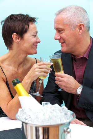 Photo of a mature married couple celebrating with a glass of champagne in a restaurant. photo