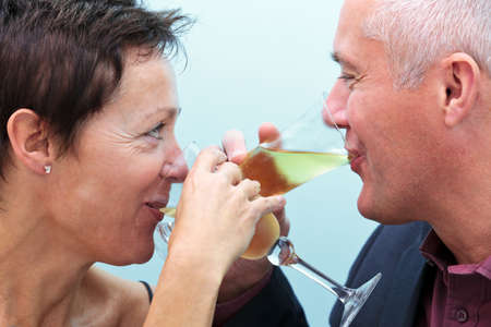 Photo of a mature married couple drinking glasses of champagne and looking into each others eyes. photo