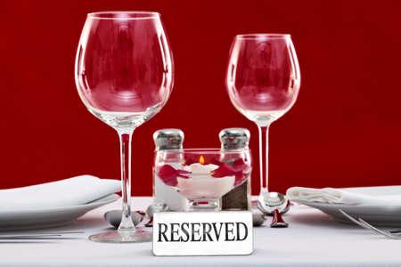 reservacion: Foto de un signo reservado en una mesa de restaurante con el fondo rojo. Foto de archivo