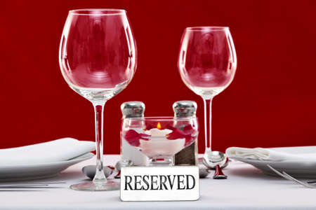 dining out: Photo of a Reserved sign on a restaurant table with red background.