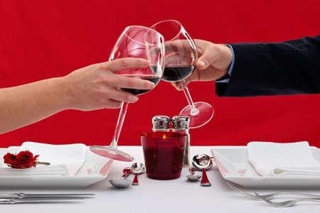 cena romantica: Foto delle mani di una coppia sposata tostare i loro bicchieri di vino su un tavolo al ristorante durante una cena romantica. Archivio Fotografico