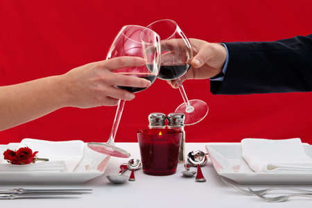 Photo of the hands of a married couple toasting their wine glasses over a restaurant table during a romantic dinner.