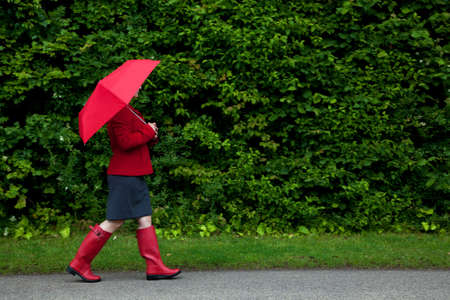 Photo of a woman in red walking along a road with her umbrella up as it starts to rain on an overcast day. Slight motion blur on her legs. photo