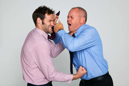 choking: Photo of two businessmen fighting against a plain background, part of a series see my portfolio for them shaking hands and hugging.