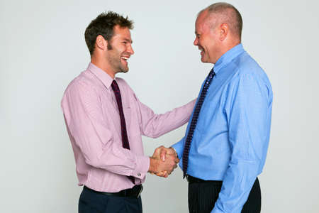 Photo of two businessmen shaking hands against a plain background, part of a series see my portfolio for images of them fighting. Stock Photo