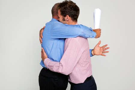 personas abrazadas: Foto de dos hombres de negocios se abrazan unas a un titular de un contrato, que forma parte de una serie de ver a mi cartera para luchar contra ellos. Foto de archivo