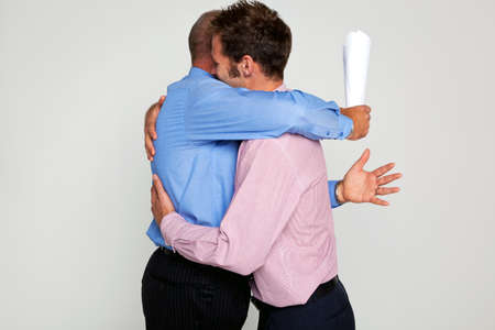 greeting people: Photo of two businessmen hugging each one holding a contract, part of a series see my portfolio for them fighting.