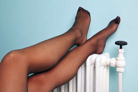 Photo of a womans legs in stockings resting on a radiator.