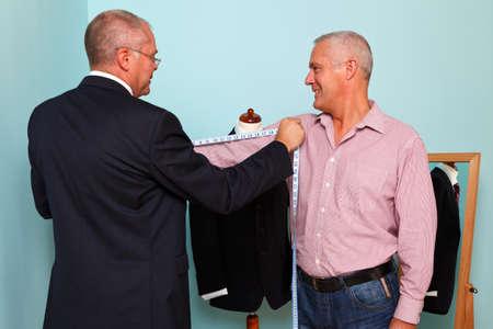 tailor measure: Foto di un sarto di misura una lunghezza del braccio mans durante il montaggio di un nuovo abito su misura Archivio Fotografico