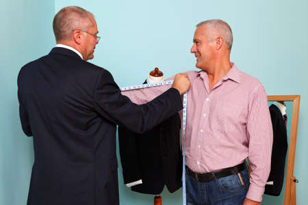 tailor shop: Photo of a tailor measuring a mans arm length during fitting for a new bespoke suit