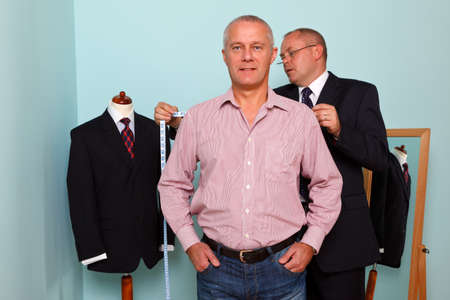tailor shop: Photo of a tailor measuring the shoulder width of a man for the fitting of a new bespoke suit