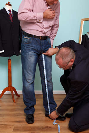 measured: Photo of a man having his inside leg measured by a tailor during a bespoke suit fitting.