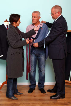 Photo of a man getting advice from his wife during a tailored bespoke suit fitting. photo