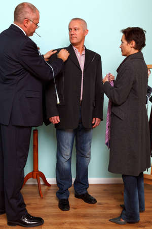Photo of a tailor drawing with chalk on the mans jacket during a bespoke suit fitting. photo