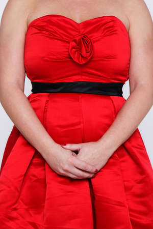 Photo of an unrecognisable woman in a red strapless party or prom dress. photo