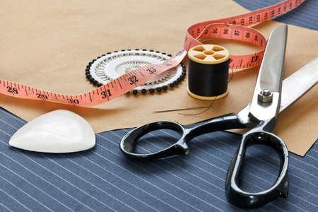 tailor measure: Ancora foto vita di abito su misura delle attrezzature per fabbricare nastri compresi, gesso, filo, forbici e spilli su un pezzo di tessuto di lana gessato. Archivio Fotografico