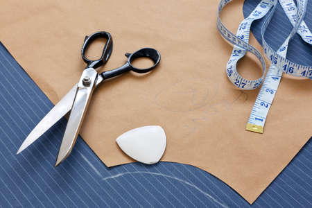 Still life photo of a suit pattern template with tape measure, chalk and scissors.