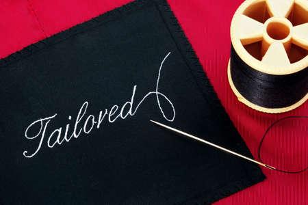 rendu: Photo d'une �tiquette du v�tement avec le mot sur mesure sur une doublure de soie rouge avec une aiguille et la bobine de fil.