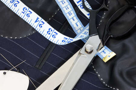 tailored: Still life photo of the inside of a bespoke suit jacket with hand stitching and scissors, tape measure, chalk and pins.