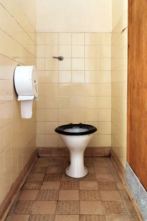 toilet bowl: Photo of a public toilet with part of the seat missing, the floor, walls and bowl are stained and dirty. Stock Photo
