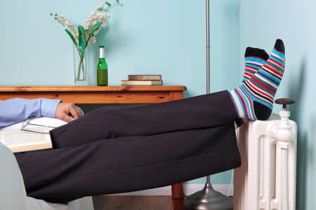 asleep chair: Photo of a man relaxing with his feet up on a radiator with a book on his lap and beer on the table