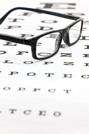 Photo of black spectacles on an eye test chart photo
