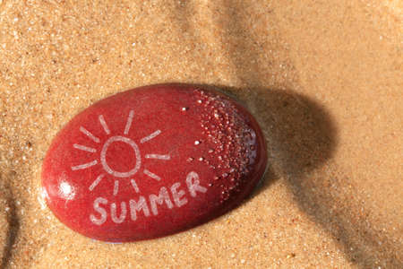 red pebble: Concept photo of a wet red pebble on a sandy beach with a drawing of the sun and the word summer on it with the late setting sunshine casting a shadow across the sand.