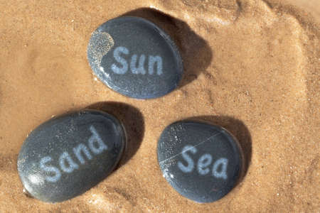 sand writing: Concept photo of Sun Sand and Sea written on wet pebbles on the beach with the sunshine casting deep shadows.
