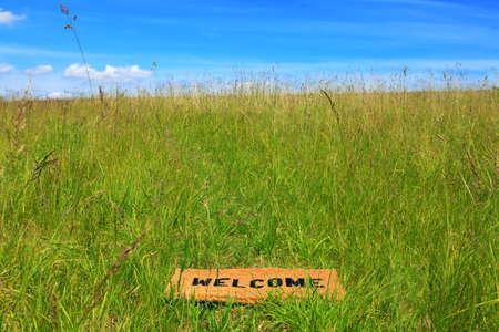 Foto de un felpudo de bienvenida en un prado de hierba en un día soleado con el cielo azul y el sol.