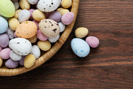 Still life photo of speckled candy covered chocolate easter eggs in a wicker basket on a rustic wooden table. photo