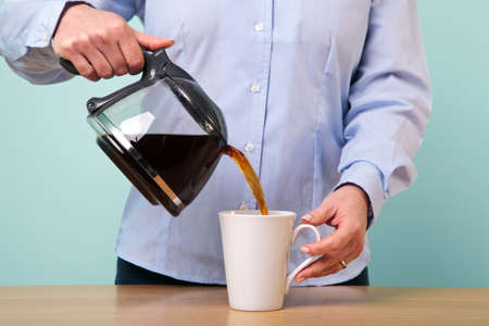 making coffee: Photo of a woman on her break pouring herself a mug of hot filtered coffee from a glass pot.