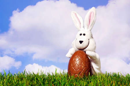 glove puppet: Fun photo of a white easter bunny puppet holding a large chocolate egg on grass with a blue cloudy sky background. Stock Photo