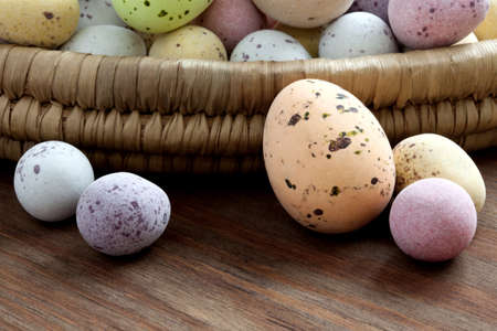 Still life photo of speckled candy covered chocolate easter eggs in a wicker basket on a rustic wooden table. Stock Photo - 12870496