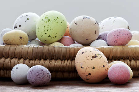 Still life photo of speckled candy covered chocolate easter eggs in a wicker basket on a rustic wooden table. Stock Photo - 12870494