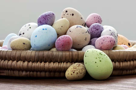Still life photo of speckled candy covered chocolate easter eggs in a wicker basket on a rustic wooden table. Stock Photo - 12870495