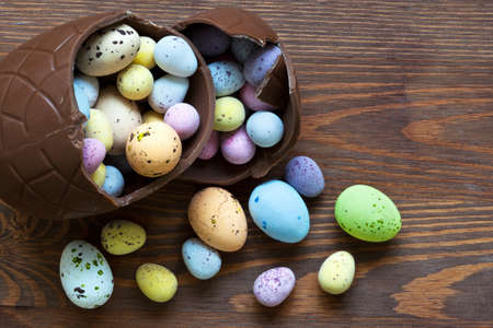 Still life photo of a large broken chocolate easter egg full of mini candy covered eggs in various pastel colours.
