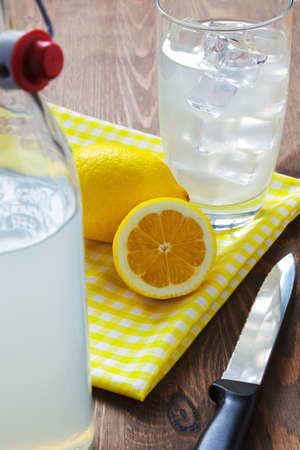 Still life photo of old fashioned or traditional homemade still lemonade with cut lemons and yellow napkin.. photo